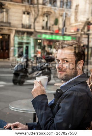 Portrait of happy smiling forty years old caucasian man in casual outfit drinking coffee in Paris cafe. City lifestyle - relax. - stock photo