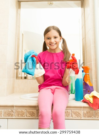 Portrait of happy smiling girl in rubber gloves posing with rag at bathroom
