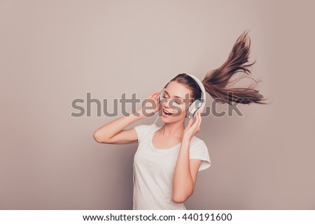 Portrait of happy smiling girl listening music in headphones and singing - stock photo