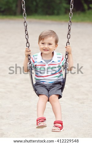 Portrait of happy smiling little boy toddler in tshirt and jeans shorts on swing on backyard playground outside on summer day, happy childhood lifestyle concept - stock photo