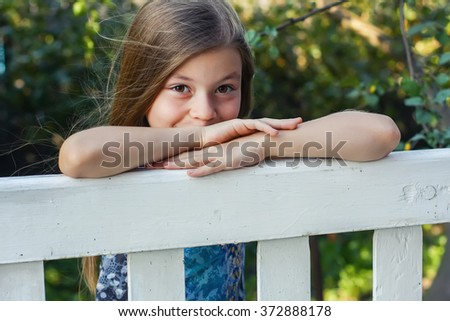 Portrait of happy smiling little girl in sunny garden in summer day. Selective focus - stock photo