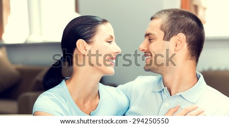 portrait of happy smiling lovely couple in blue casual smart clothing, looking at each other, at home - stock photo