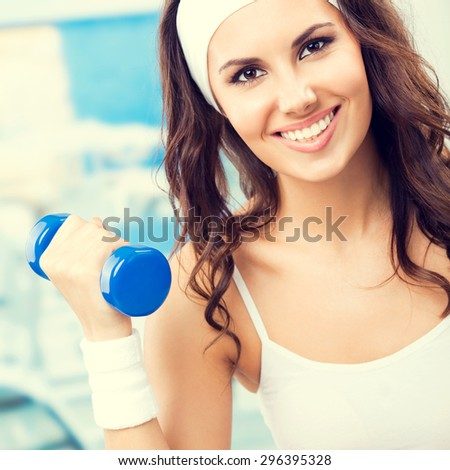 Portrait of happy smiling lovely woman exercising with dumbbell, at fitness center or gym