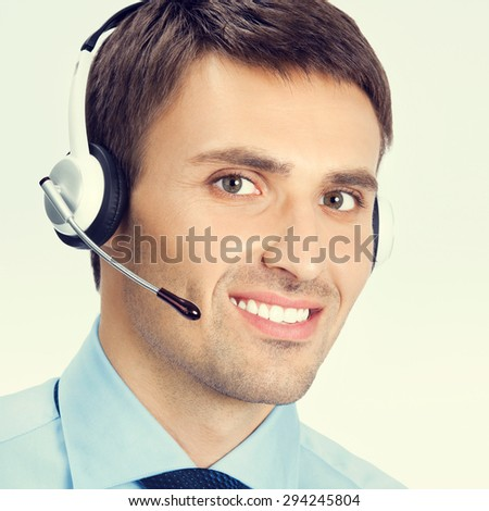 Portrait of happy smiling male customer support phone operator in headset, in blue confident business wear - stock photo