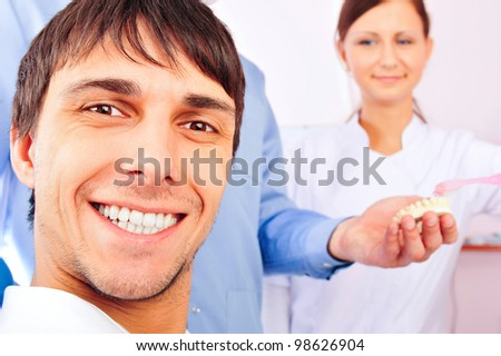 Portrait of happy smiling male patient and doctor with his assistant at office. Focus on man. - stock photo