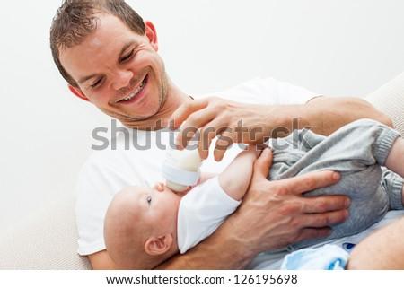 Portrait of happy smiling man feeding baby boy. - stock photo