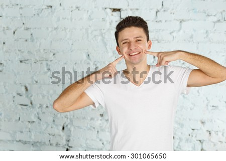 Portrait of happy smiling man. Happy man smiling - friendly face. Young cheerful man in a white shirt shows smile. Young handsome man smiling. Male model looking at camera. Copy space. - stock photo
