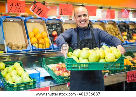 Portrait of happy smiling mature man in apron selling seasonal fruits at market