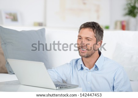 Portrait of happy smiling mature man with laptop in house