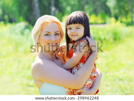 Portrait of happy smiling mother and child together outdoors in summer sunny day - stock photo