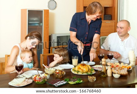 Portrait of happy smiling multigeneration family communicate over holiday table at home interior