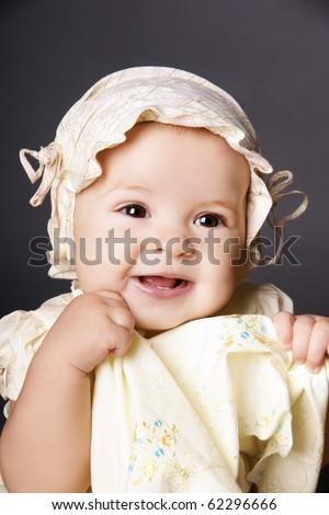 Portrait of happy smiling pretty baby girl in hat, studio shot - stock photo