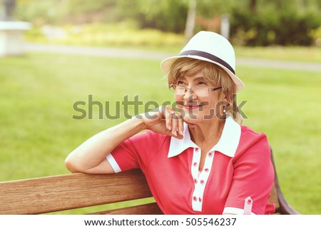 Portrait of happy smiling senior woman sitting on a bench outside on sunny day