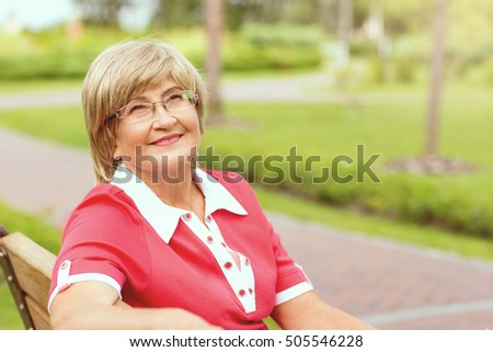 Portrait of happy smiling senior woman sitting on a grass outside on sunny day