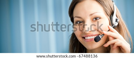 Portrait of happy smiling support phone operator in headset at workplace. You can use left part for slogan, big text or banner.