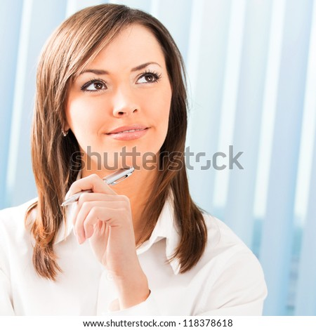 Portrait of happy smiling thinking business woman at office - stock photo