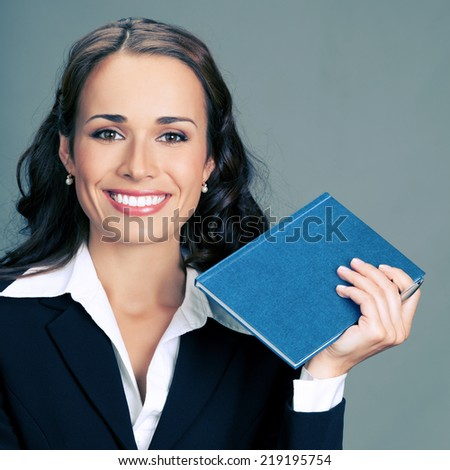 Portrait of happy smiling thinking business woman with blue notepad or organizer, over gray background - stock photo