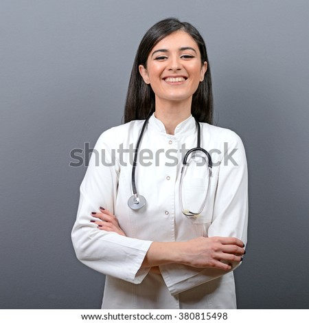 Portrait of happy smiling woman doctor against gray background - stock photo