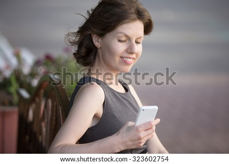 Portrait of happy smiling woman holding cellphone in hands, using app on street in summer, sitting on bench in park, looking at screen, reading message, typing text with cheerful expression - stock photo