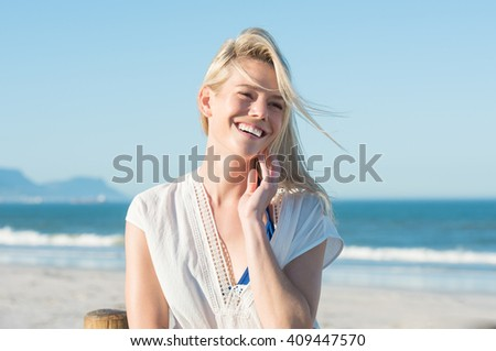 Portrait of happy smiling woman on the beach. Smiling sensual blonde posing on a beautiful wild beach. Pretty girl in casaul looking away and laughing. - stock photo