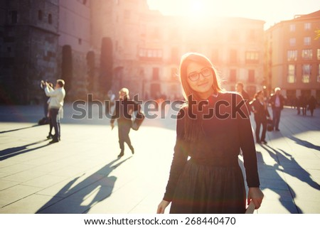 Portrait of happy smiling woman standing on the square on sunny summer or spring day outside, cute smiling woman looking at you, attractive young girl enjoying summer, filtered image, flare sunshine - stock photo