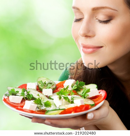Portrait of happy smiling woman with plate of salad, outdoor - stock photo