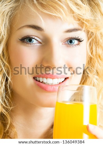 Portrait of happy smiling young beautiful blond woman drinking orange juice - stock photo