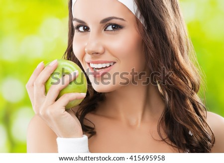 Portrait of happy smiling young beautiful brunette woman in fitness wear with apple, outdoors. Healthy lifestyle, beauty and dieting concept. - stock photo