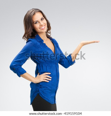 Portrait of happy smiling young beautiful businesswoman showing something or blank copyspase for product or sign text