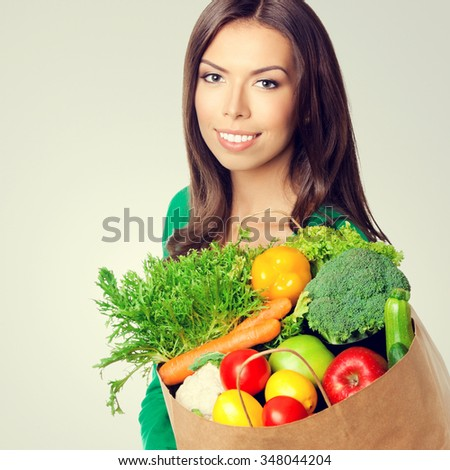 Portrait of happy smiling young beautiful lovely woman with shopping bag of healthy vegetarian raw food, with copyspace blank empty area for text or slogan - stock photo