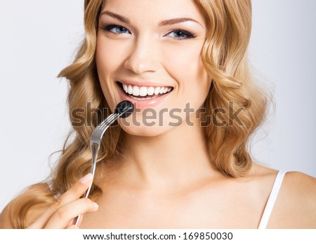 Portrait of happy smiling young beautiful woman eating black olive, over gray background