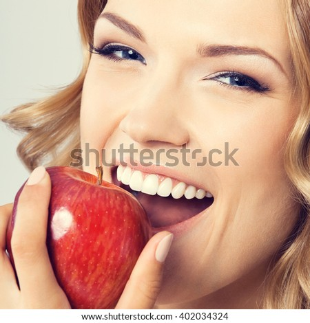 Portrait of happy smiling young beautiful woman eating red apple - stock photo