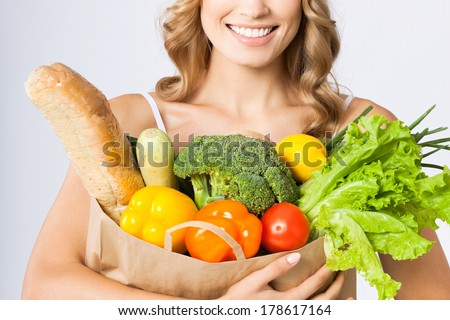 Portrait of happy smiling young beautiful woman holding grocery shopping bag with healthy vegetarian raw food, over gray background - stock photo