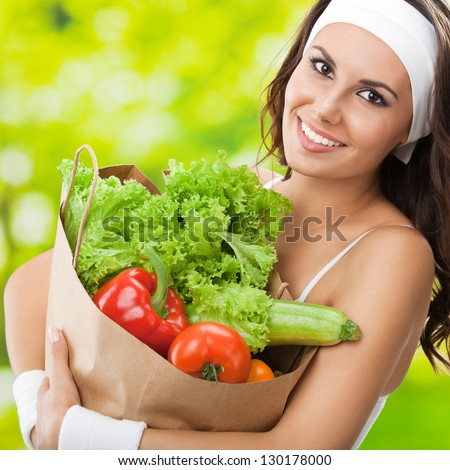 Portrait of happy smiling young beautiful woman in fitness wear holding grocery shopping bag with healthy vegetarian food, outdoors - stock photo