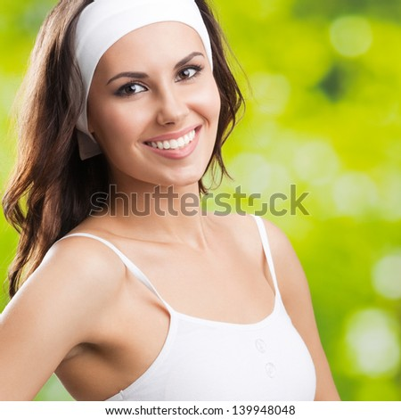 Portrait of happy smiling young beautiful woman in fitness wear, outdoors - stock photo