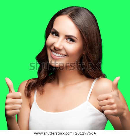 Portrait of happy smiling young beautiful woman in white casual clothing, showing thumbs up gesture, isolated over green screen chroma key background - stock photo