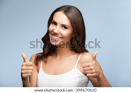 Portrait of happy smiling young beautiful woman in white casual clothing, showing thumbs up gesture, over grey background - stock photo