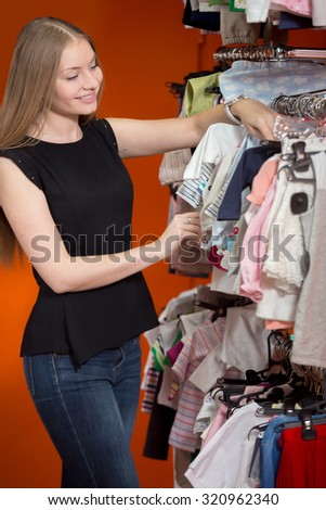 Portrait of happy smiling young beautiful woman shopping, standing in department store in front of rack with baby clothes, choosing new outfit for toddler child, looking through hangers - stock photo