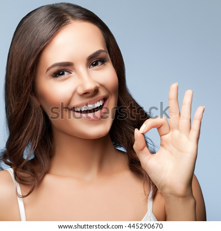 Portrait of happy smiling young beautiful woman showing okay or zero hand gesture, over grey background - stock photo