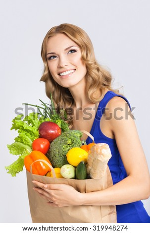 Portrait of happy smiling young beautiful woman with healthy vegetarian raw food, over gray background