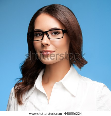 Portrait of happy smiling young brunette businesswoman in glasses, over blue background