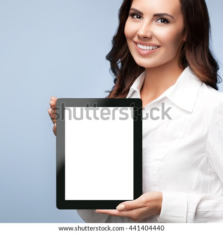 Portrait of happy smiling young brunette businesswoman showing blank no-name tablet pc monitor, over grey background, with copyspace area for slogan or text message - stock photo