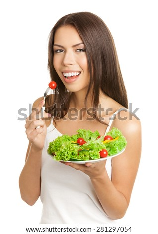 Portrait of happy smiling young brunette woman eating vegetarian salad with cherry tomatoes, in tank top casual smart clothing, isolated over white background