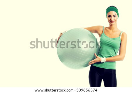 portrait of happy smiling young brunette woman in green fitness wear with fitball, with blank copyspace area for slogan or text - stock photo