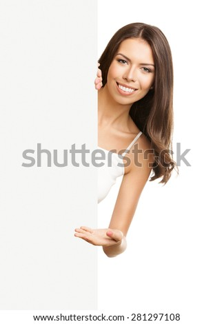 Portrait of happy smiling young brunette woman in tank top casual smart clothing, showing empty blank signboard with copyspace area for text or slogan, isolated against white background - stock photo