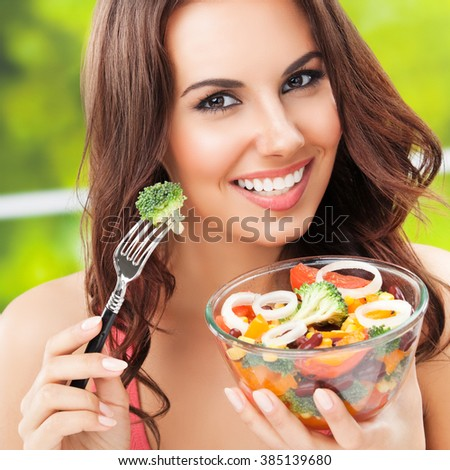Portrait of happy smiling young brunette woman with vegetarian vegetable salad, with copyspace - stock photo