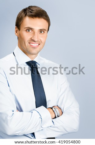 Portrait of happy smiling young business man, over grey background - stock photo