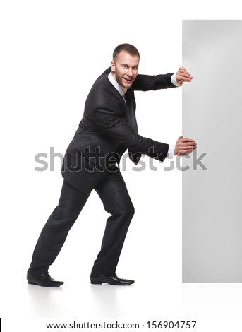 Portrait of happy smiling young business man pushing blank signboard isolated on white background
