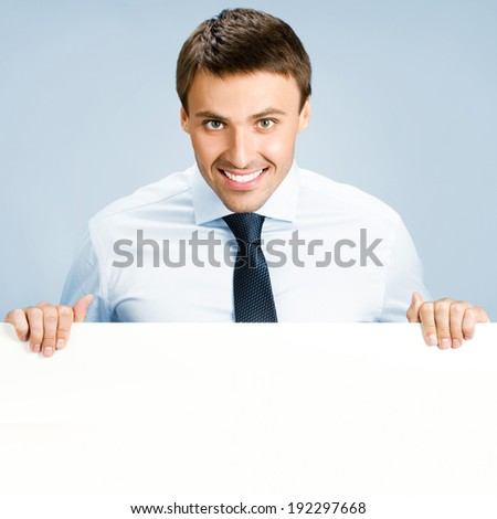 Portrait of happy smiling young business man showing blank signboard, over blue background - stock photo