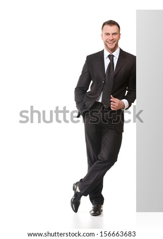 Portrait of happy smiling young business man with blank signboard isolated on white background